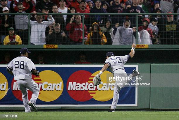 New York Yankees' right fielder Bobby Abreu reaches out to snare a ball hit deep to right in the ninth inning of a game against the Boston Red Sox at...