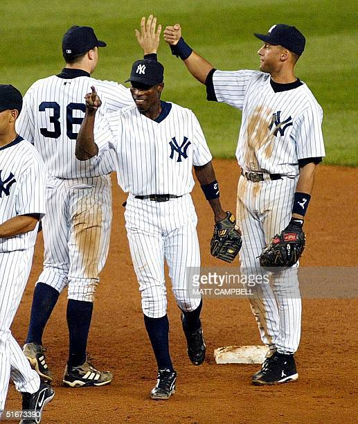 New York Yankees' second baseman Alfonso Soriano smiles as he and teammates Derek Jeter Nick Johnson celebrate the Yankees 43 come from behind win...