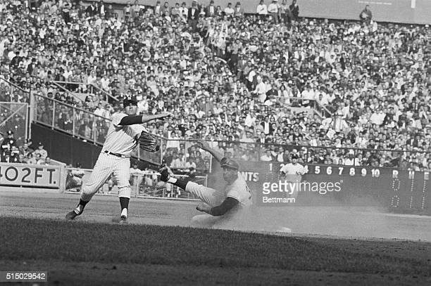 New York Yankees' second sacker Bobby Richardson Hurls towards first as Orlando Cepeda of the San Francisco Giants slides spikes high into second...