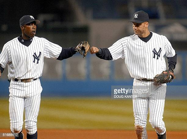 New York Yankees' shortstop Derek Jeter and second baseman Alfonso Soriano slap hands at the end of the sixth inning at Yankee Stadium in New York 21...