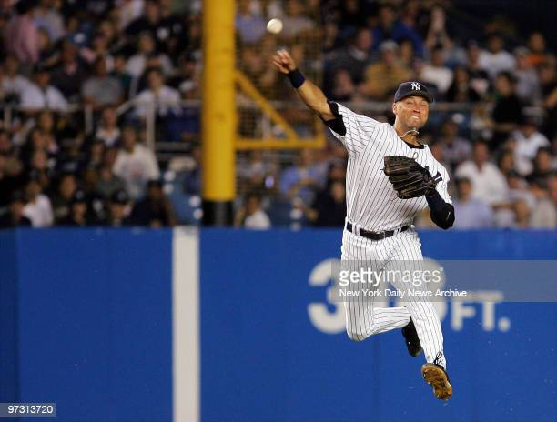 New York Yankees' shortstop Derek Jeter makes a leaping throw to first in the sixth inning of a game against the Atlanta Braves at Yankee Stadium The...