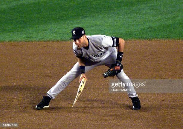 New York Yankees' shortstop Derek Jeter picks up the broken bat of New York Mets Kurt Abbott during the 4th inning of Game Five of the World Series...