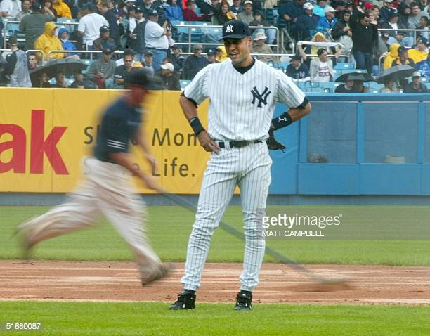 New York Yankees shortstop Derek Jeter waits as the grounds crew tries to dry off the infield between innings 02 September 2002 as the Yankees played...