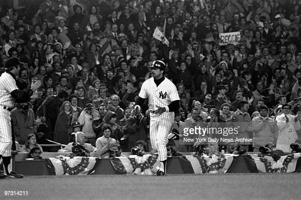 New York Yankees' slugger Reggie Jackson nonchalantly trots toward home plate past all the beautiful World series bunting and a few score of the...