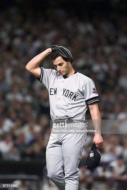 New York Yankees' starter Andy Pettitte holds his head as he walks off mound after giving up one run in the first inning of Game 6 of the World...