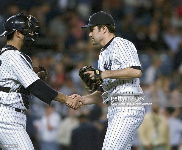 New York Yankees' starter Mike Mussina shakes hands with catcher Jorge Posada after pitching a twohit completegame shutout against the Tampa Bay...