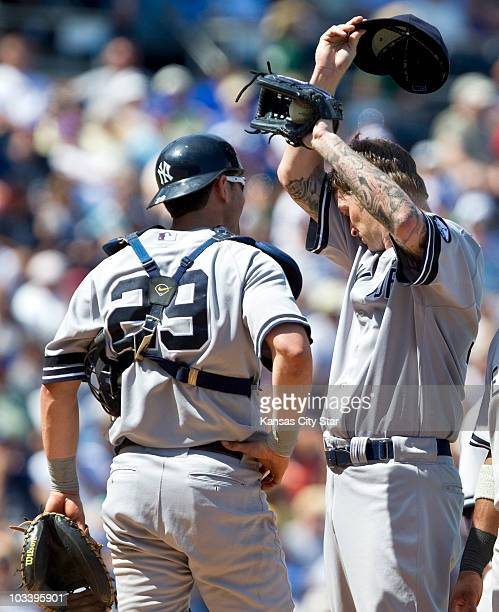 New York Yankees starting pitcher AJ Burnett wipes the sweat away from his face as catcher Francisco Cervelli visits the mound in eighthinning action...