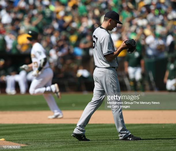 New York Yankees starting pitcher AJ Cole walks off the mound after giving up solo home run to Oakland Athletics' Mark Canha in the fifth inning of...