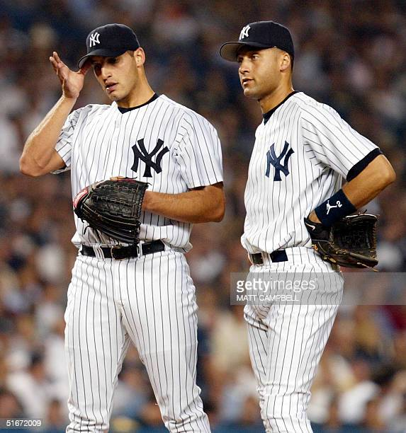 New York Yankees' starting pitcher Andy Pettitte wipes his brow while shortstop Derek Jeter awaits a conference on the pitcher's mound after Pettitte...