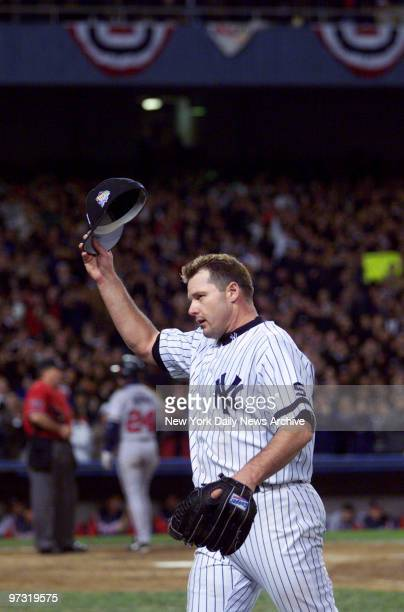 New York Yankees' starting pitcher Roger Clemens tips his hat as he leaves in the eighth inning with two on during Game 4 of the World Series between...