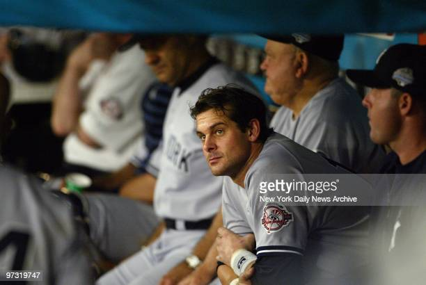 New York Yankees' third baseman Aaron Boone with manager Joe Torre and bench coach Don Zimmer in the background watches glumly from the dugout as the...