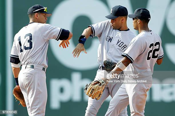 New York Yankees' third baseman Alex Rodriguez shortstop Derek Jeter and second baseman Robinson Cano celebrate on the field after defeating the...