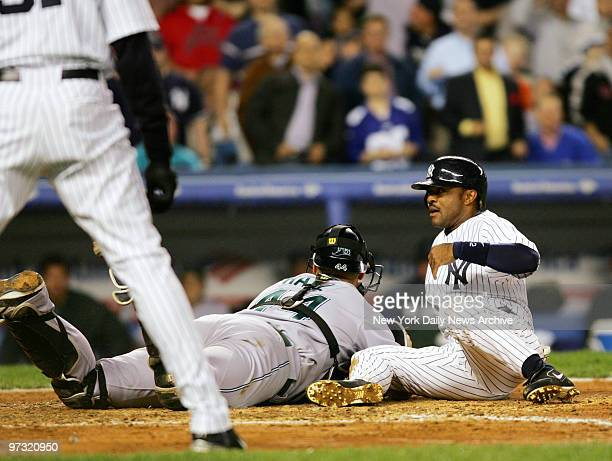 New York Yankees' Tony Womack slides into the tag of Tampa Bay Devil Rays' catcher Toby Hall for the third out while trying to score from first on a...