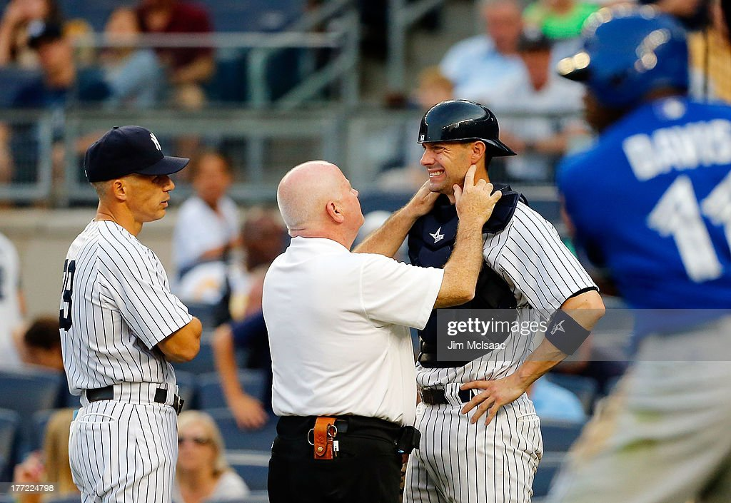 New York Yankees trainer Steve Donahue and manager Joe Girardi #28 check on catcher Chris Stewart #19 after he was hit in the mask with a ball in the seventh inning against the Toronto Blue Jays at Yankee Stadium on August 22, 2013 in the Bronx borough of New York City.