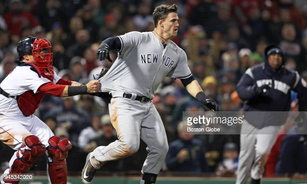 New York Yankees' Tyler Austin charges the mound against Red Sox pitcher Joe Kelly after he was knocked down in the seventh inning Red Sox catcher...