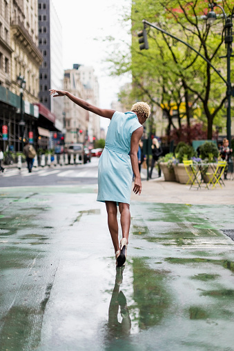 USA, New York, young blonde african-american woman walking in puddle - gettyimageskorea