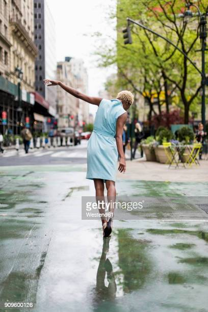 USA, New York, young blonde african-american woman walking in puddle