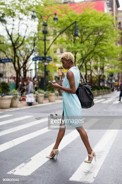 usa, new york, young blonde african-american woman with cup of coffee and smart phone crossing street - afro amerikaanse etniciteit stockfoto's en -beelden