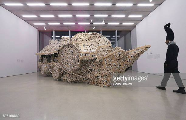 New Yorkbased Haitian artist Engels views a mixed media art installation by Hew Locke of Guyana on exhibit at Perez Art Museum Miami during the 15th...