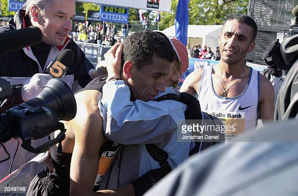 New Yorker Khalid Khannouchi fist place men's finisher hugs fifth place finisher Abdelkhader El Mou at the finish line during the Chicago Marathon on...