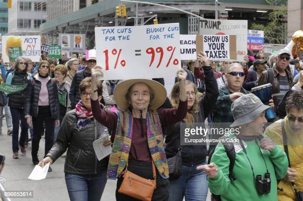 New Yorkers and visiting demonstrators protest during a march on Tax Day demanding that President Donald Trump release his tax returns at Sixth...
