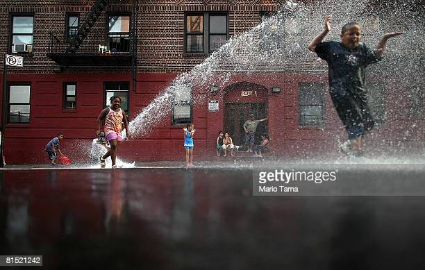New Yorkers cool off with the help of a fire hyrdrant June 10 2008 in the Bronx borough of New York City Temperatures reached into the upper 90's...