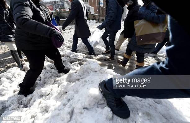 New Yorkers cross snow drifts on Park Avenue in midtown Manhattan on March 15 2017 the morning after Winter Storm Stella dumped snow and sleet in New...