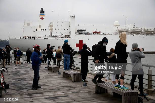 New Yorkers greet the USNS Comfort hospital ship traveling north on the Hudson River as it heads to Pier 90 on March 30 2020 seen from pier 86 in New...