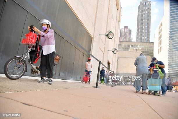 New Yorkers in need receive free produce dry goods and meat at a Food Bank For New York City distribution event at Lincoln Center on July 29 2020 in...