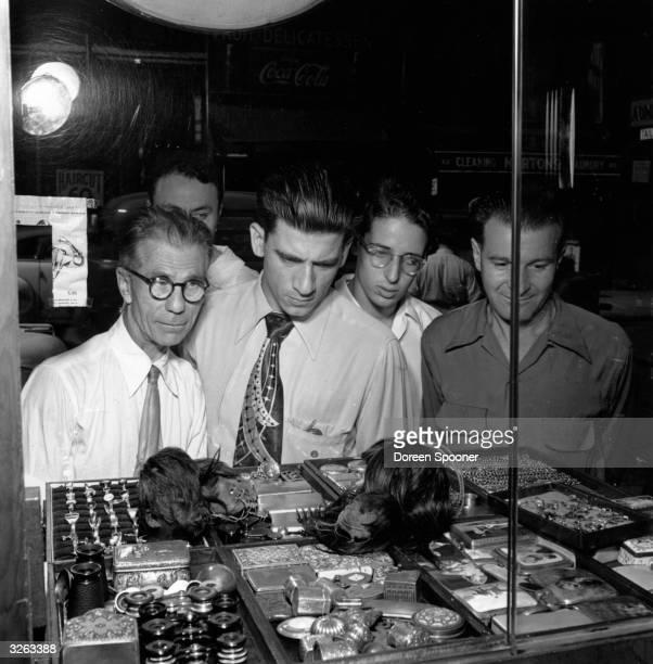 New Yorkers looking in at Rosenburg's window at the little shrunken Jivaro human heads on display amongst various trinkets