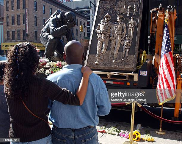 New Yorkers Phil Dusek and Lydia Cordero gaze at a bronze memorial sitting atop a flatbed truck in New York City Wednesday Sept 19 2001 The State of...