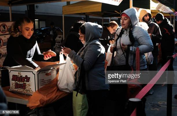 New Yorkers receive special Thanksgiving groceries including a turkey at the Reaching Out Community Services food pantry on November 20 2017 in the...