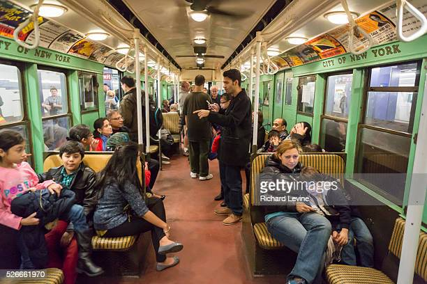 New Yorkers tourists and subway buffs travel on a vintage MTA Nostalgia Train Christmas season ride on Sunday December 27 2015 The straps ceiling...