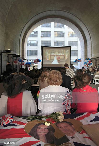 New Yorkers watch live coverage of the royal wedding projected on a giant screen under the archway of the Manhattan Bridge during the Royal Wedding...