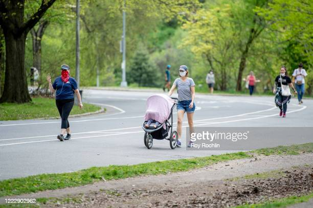 New Yorkers wear protective masks and practice social distancing at Prospect Park in Brooklyn during the coronavirus pandemic on May 04, 2020 in New...