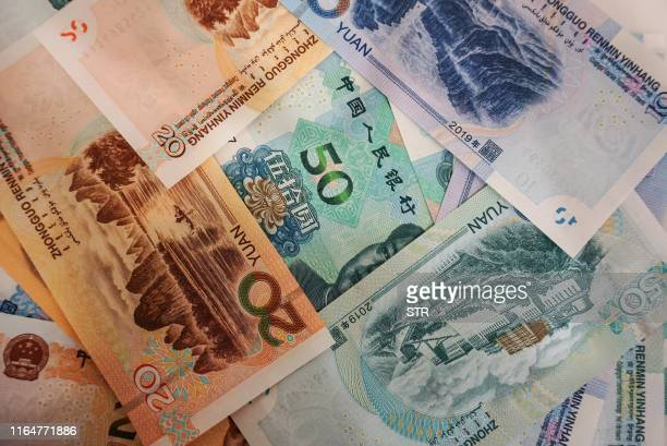New yuan banknotes are seen on a table at a bank counter in Hangzhou in China's eastern Zhejiang province on August 30 as the Peoples Bank of China...