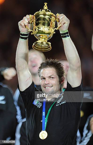 New Zealand All Blacks captain Richie McCaw holds the Webb Ellis cup as he stands with his players after the 2011 Rugby World Cup final match New...