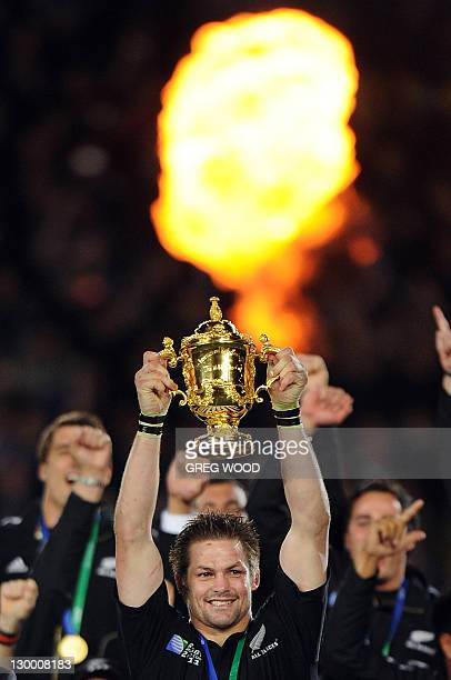 New Zealand All Blacks captain Richie McCaw holds the Webb Ellis cup together with his players after the 2011 Rugby World Cup final match New Zealand...