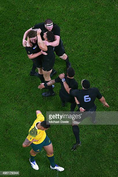New Zealand All Blacks players celebrate as Israel Folau of Australia walks off dejected after the 2015 Rugby World Cup Final match between New...