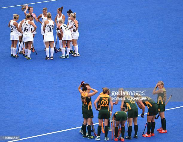 New Zealand and South African players wait a for video referral decision to a penalty corner decision by unseen umpire Chieko Soma of Japan during...