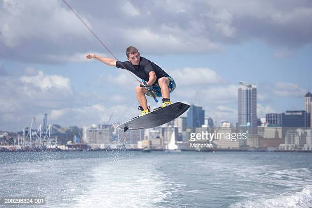 new zealand, auckland, young man wakeboarding in harbour - waterskiing stock photos and pictures