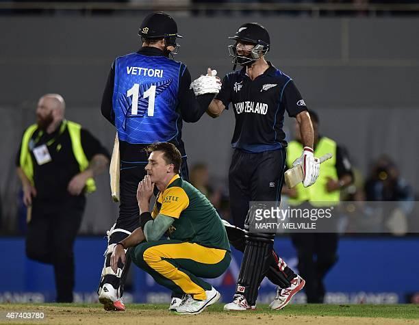 New Zealand batsman Grant Elliott celebrates with teammate Daniel Vettori following their win as South African bowler Dale Steyn sits dejected during...