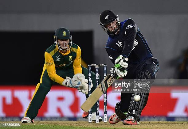 New Zealand batsman Martin Guptill plays a shot as South African wicketkeeper Quinton de Kock looks on during the Cricket World Cup semi-final match...