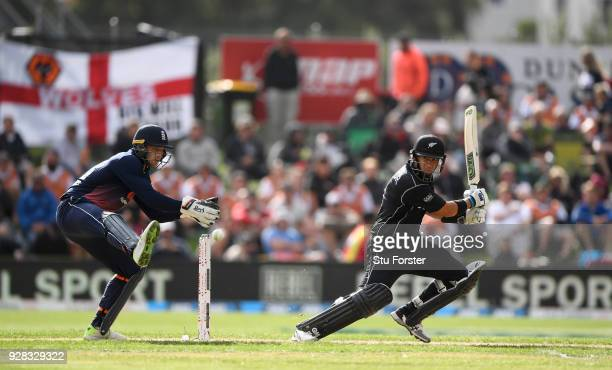 New Zealand batsman Ross Taylor hits out watched by Jos Buttler during the 4th ODI between New Zealand and England at University of Otago Oval on...