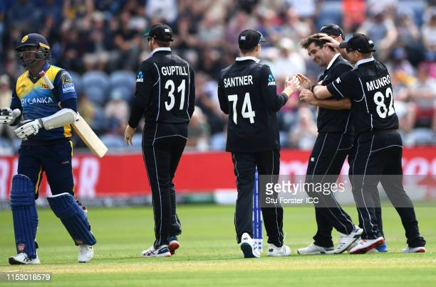 New Zealand bowler Colin de Grandhomme is congratulated by team mates after dismissing Angelo Mathews during the Group Stage match of the ICC Cricket...