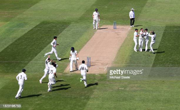 New Zealand bowler Matt Henry celebrates with team mates after taking the wicket of England opening batsman Rory Burns for 0 during day three of the...