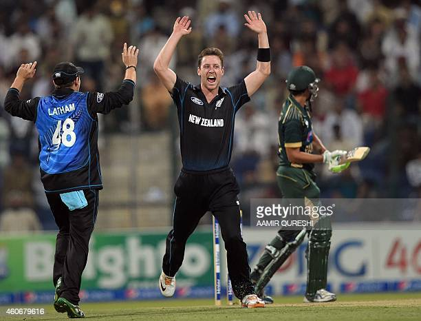 New Zealand bowler Matt Henry celebrates with teammate Tom Latham after taking the wicket of Pakistani batsman Younis Khan during the fifth and final...