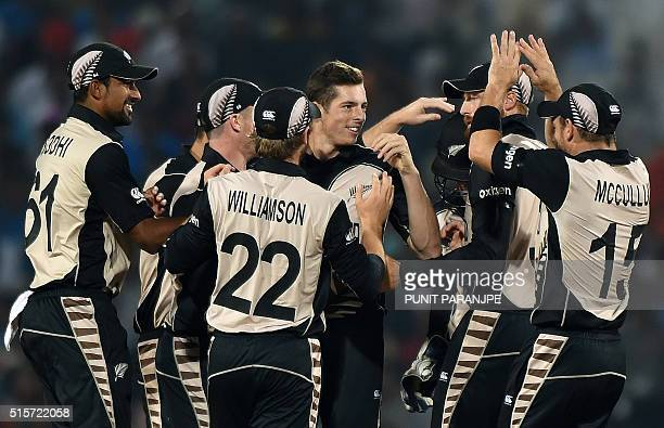 New Zealand bowler Mitchell Santner celebrates with team mates after the wicket of India's batsman Rohit Sharma during the World T20 cricket...