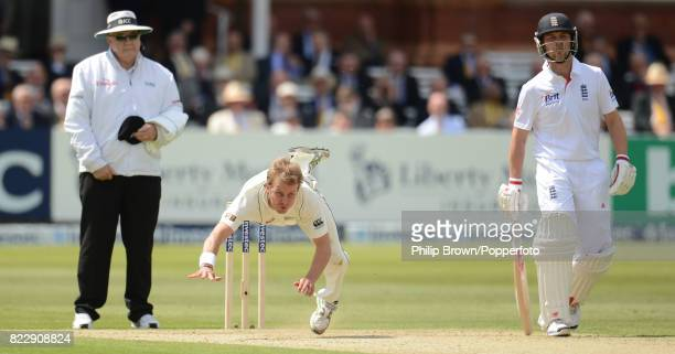 New Zealand bowler Neil Wagner falls over after bowling the ball watched by umpire Steve Davis and England's nonstriking batsman Jonathan Trott...