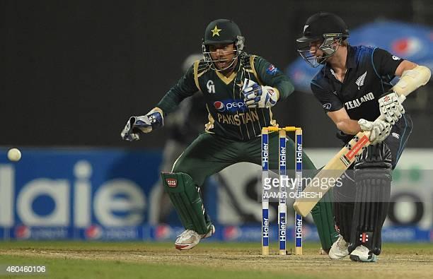 New Zealand captain Kane Williamson plays a shot as Pakistani wicketkeeper Sarfraz Ahmed looks on during the third DayNight International cricket...